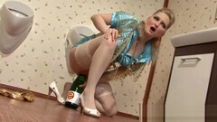 Blonde girl riding champain bottle in toilet Thumb
